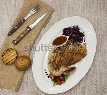 Juicy roast chicken with vegetables and ketchup. Served on porcelain plate on a tablecloth with fork Stock photo © mcherevan
