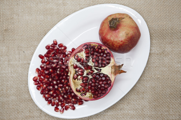 Pomegranates have broken into pieces with red berries on a porcelain plate on a textile background. Stock photo © mcherevan