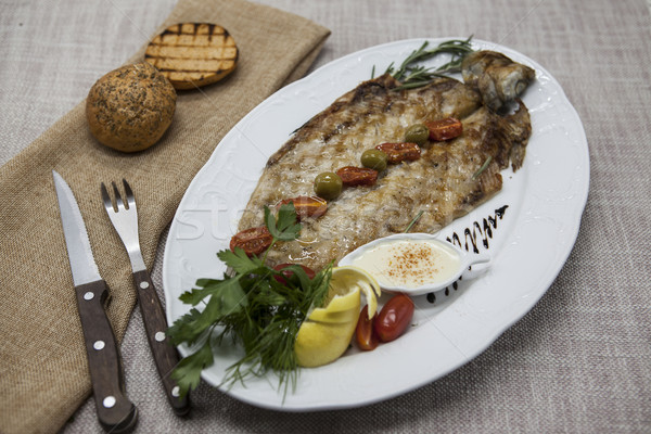 Fried fish whitefish on plate with vegetables and bread with a fork and knife. Stock photo © mcherevan