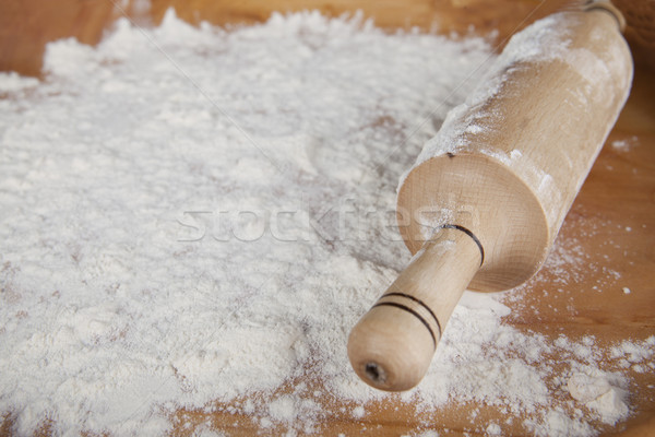 Rolling pin on flour on a wooden tray. Stock photo © mcherevan