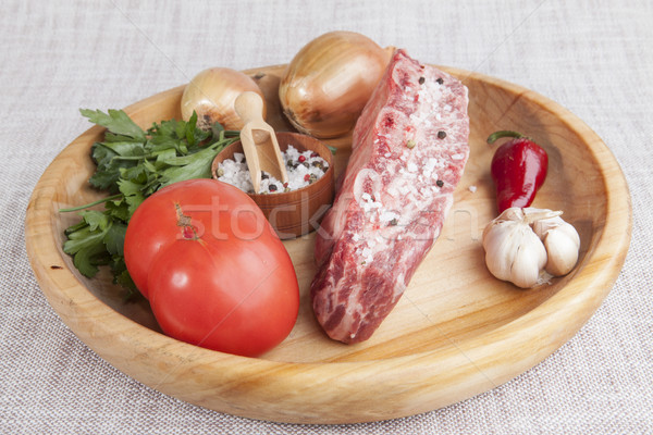 A piece of fresh marbled beef, chili pepper, parsley, onion, garlic, ribs lie on a wooden tray Stock photo © mcherevan