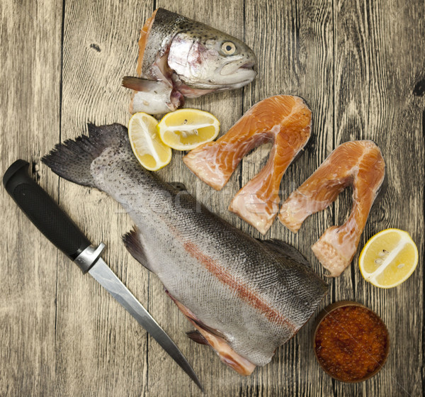 Fresh Norwegian rainbow trout with lemon red caviar, sea salt, knife and onions on a wooden backgrou Stock photo © mcherevan