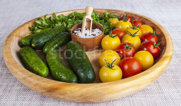 Fresh red and yellow cherry tomatoes and cucumbers with salt shaker on wooden tray in a rustic style Stock photo © mcherevan