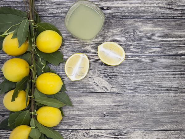 Fresh juicy lemons and a glass of homemade lemonade on a wooden background Stock photo © mcherevan