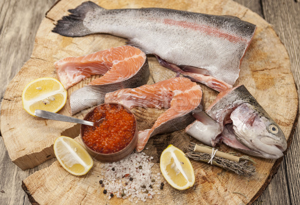 Fresh Norwegian rainbow trout with lemon red caviar, and onions on a wooden background Stock photo © mcherevan