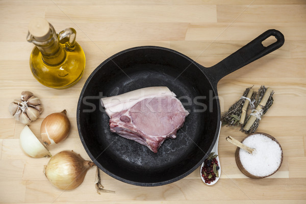A piece of delicious fresh raw pork close-up on a cast-iron frying pan, onions, garlic, spices, salt Stock photo © mcherevan