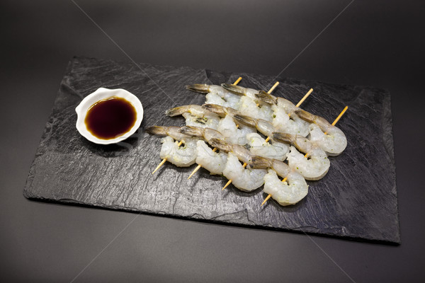Tiger shrimps shish kebabs of teriyaki on a stone plate with soy sauce. Stock photo © mcherevan