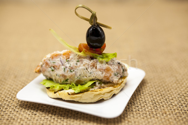 Fresh Spanish tapas on bread baguette smoked Norwegian salmon with black olive butter, herbs and oni Stock photo © mcherevan
