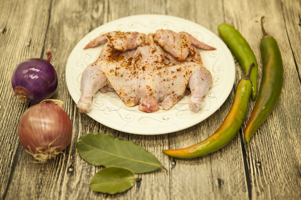 Raw fresh chicken on porcelain plate with lemon and chilli onion   on the wooden background Stock photo © mcherevan