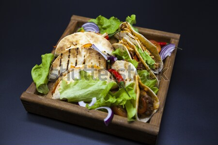 Mexican Tortilla with meat, beef and stewed vegetables and spicy sauce on a wooden tray. Stock photo © mcherevan