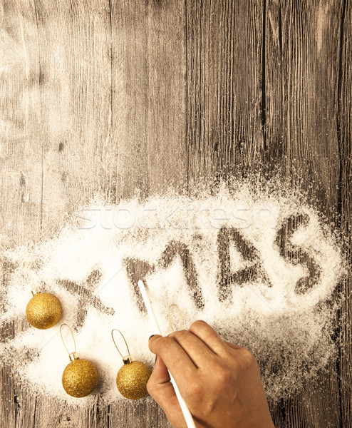 Christmas card with a female hand writing xmas, gold balls in the snow on a wooden background. Stock photo © mcherevan
