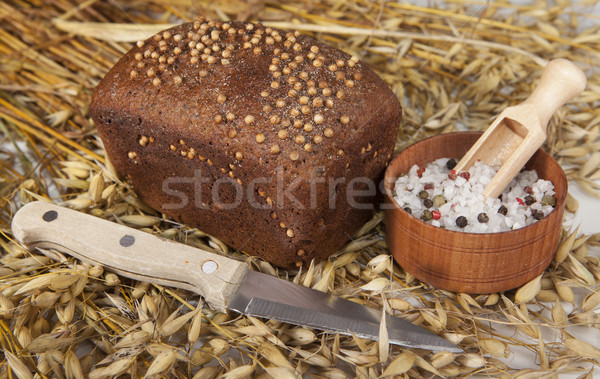 Loaf of homemade bread with black mustard seeds on a table with spikelets of rye oats and salt shake Stock photo © mcherevan