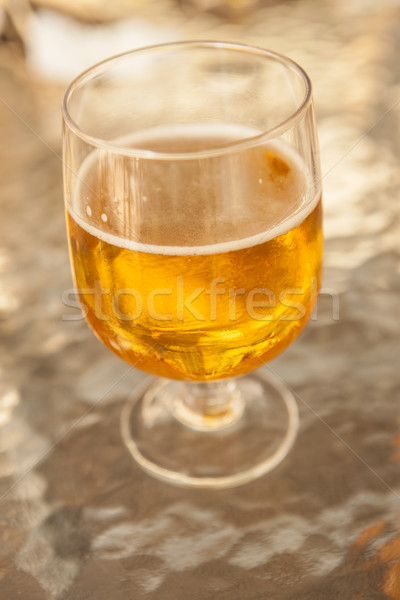 Misted glass of beer on a glass table in a bar Stock photo © mcherevan