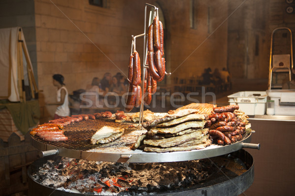 Gourmet meat pieces pork ribs, sausages, on a large grill . Stock photo © mcherevan