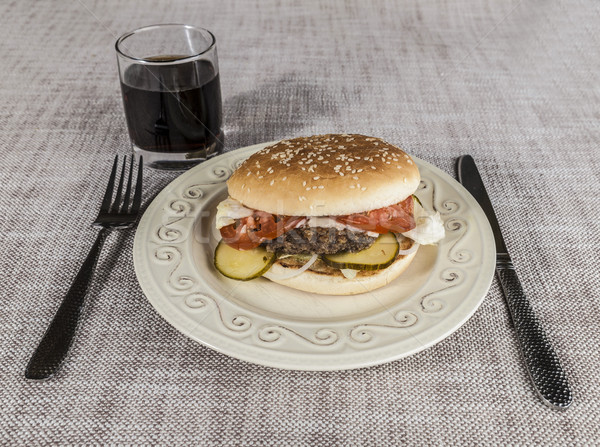Fresh hamburger with a chop of marbled beef and fresh vegetables on a plate with a fork and knife Stock photo © mcherevan
