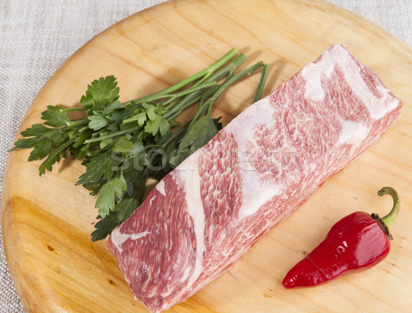 A piece of fresh marbled beef, chili pepper, parsley, ribs lie on a wooden tray Stock photo © mcherevan