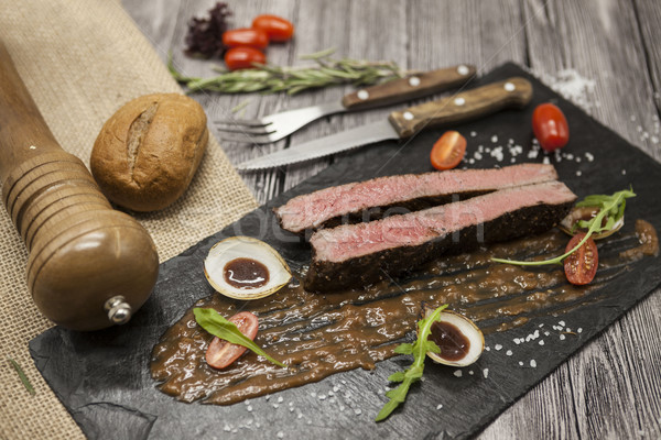 Ribeye steak from marble beef meat with vegetables and barbecue sauce. Served on a plate of black st Stock photo © mcherevan