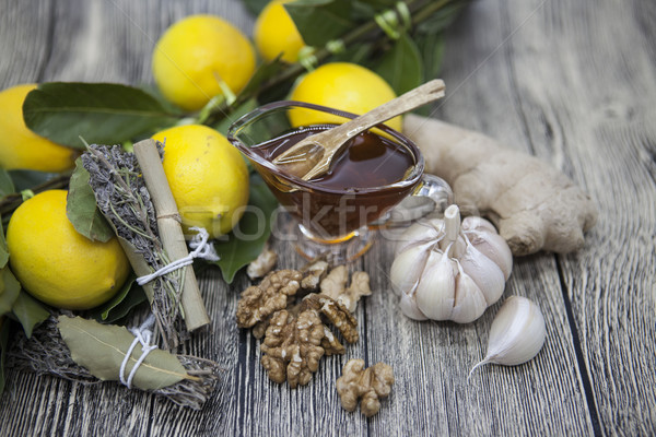 The composition of glass vase with floral honey and wooden spoon with lemon provencal herbs walnuts, Stock photo © mcherevan