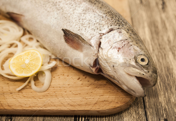 Fresh Norwegian rainbow trout with lemon and onions on a wooden background Stock photo © mcherevan