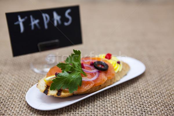TAPAS poster . Fresh Spanish tapas on bread baguette smoked Norwegian salmon with black olive butter Stock photo © mcherevan