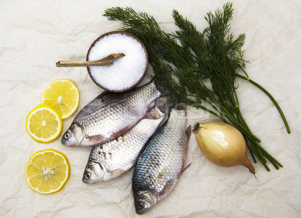 A  fresh carp live fish lying on a on paper background with a knife and slices of lemon and with sal Stock photo © mcherevan