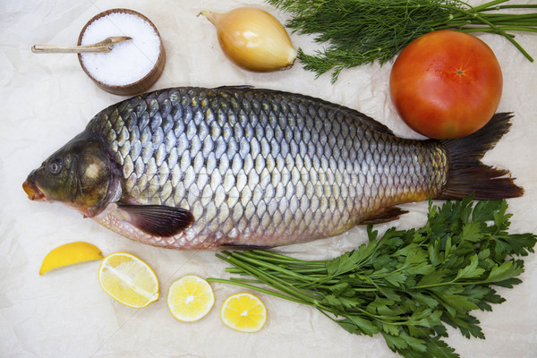A large fresh carp live fish lying on a on paper background with a knife and slices of lemon and wit Stock photo © mcherevan