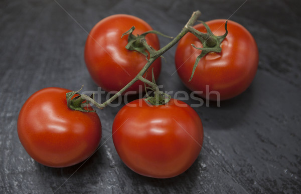 Fresh branch of red Sicilian ripe tomatoes on a stone background Stock photo © mcherevan