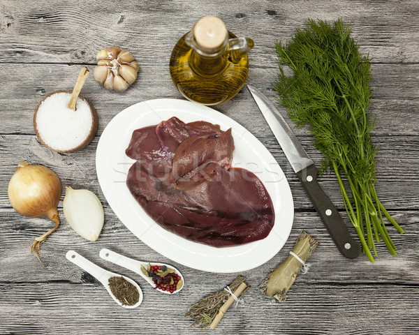 Pieces of fresh raw beef liver, onion, garlic, spices, dill, parsley, salt, knife, olive oil on porc Stock photo © mcherevan