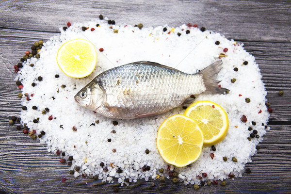 Stock photo: A  fresh carp live fish lying on a on salt and pepper background with slices of lemon and with salt