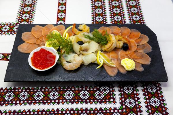 Banquet menu. Fish assortment on a beautiful black platter with red fish, shrimp, caviar, smoked sal Stock photo © mcherevan