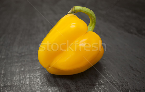 Fresh juicy yellow sweet pepper close up on a stone background. Stock photo © mcherevan