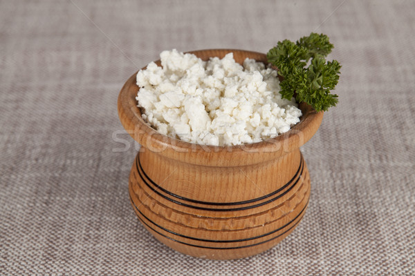 Homemade cottage cheese in a small wooden pot on linen tablecloths Stock photo © mcherevan