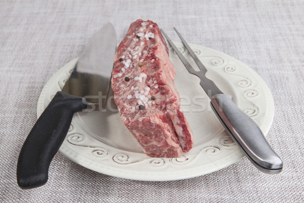 A piece of fresh marbled beef with sea salt and black pepper, knife and fork on a porcelain plate Stock photo © mcherevan