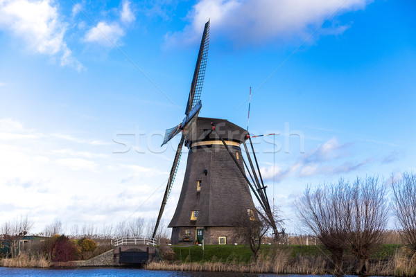 Old, traditional windmill in the Dutch canals. Netherlands.White clouds on a blue sky, the wind is b Stock photo © mcherevan