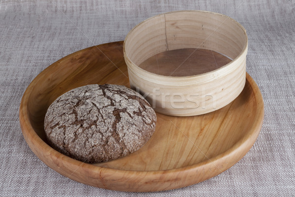 Fresh homemade bread made from durum wheat, rye, on a wooden tray with a sieve for flour.  Stock photo © mcherevan