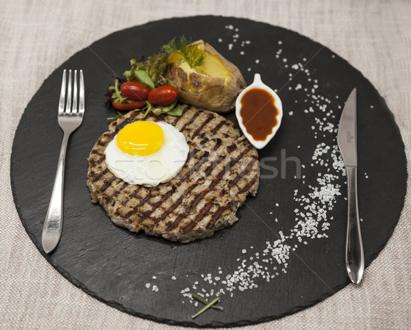 Big juicy grilled steak marbled beef with egg baked potatoes with barbecue sauce. Served on a stone  Stock photo © mcherevan