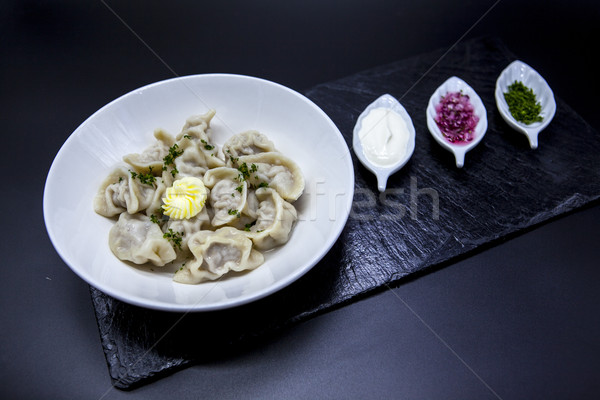 Traditional cooked Russian dumplings with meat of pork in the dish with sour cream, onions, spices o Stock photo © mcherevan