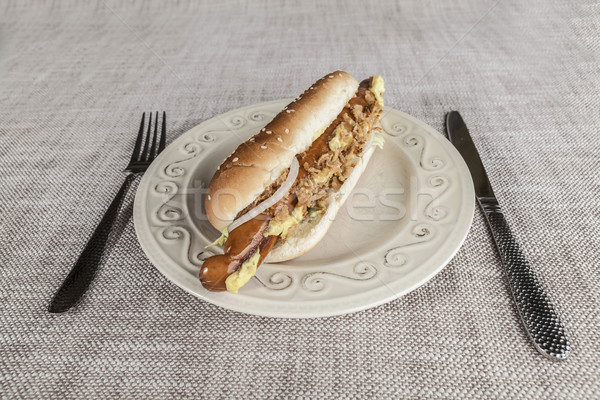 Fresh tasty hot dog with fried onions and fresh lettuce with mustard on a porcelain plate with fork  Stock photo © mcherevan