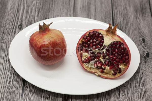 Pomegranates have broken into pieces with red berries on a porcelain plate on a dark background. Stock photo © mcherevan