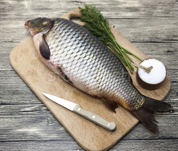 A large fresh carp live fish lying on a wooden board with salt and dill. Stock photo © mcherevan