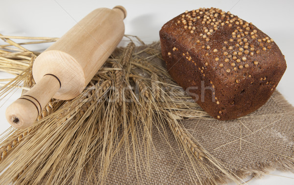 Loaf of homemade bread with black mustard seeds on a table with spikelets of rye and a wooden rollin Stock photo © mcherevan