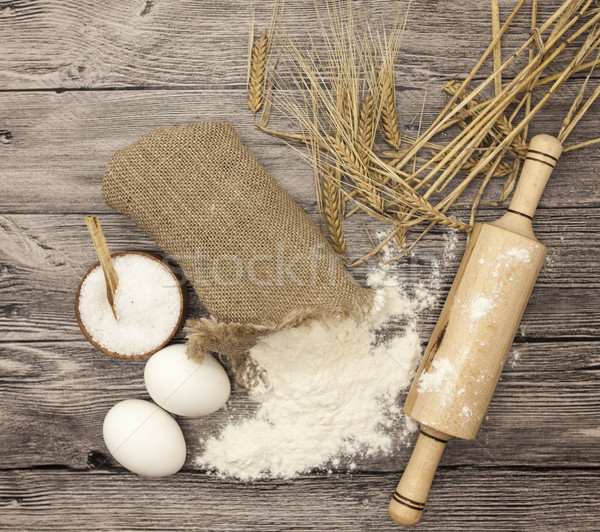 Wheat flour in a canvas bag, with spikelets of rye, a large salt shaker wood, raw eggs, a wooden rol Stock photo © mcherevan