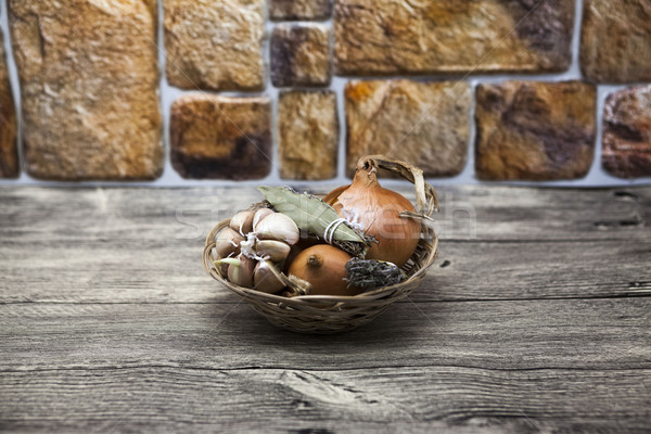 Spice set in wicker basket onion, Provence herbs, garlic at the table in the kitchen Stock photo © mcherevan