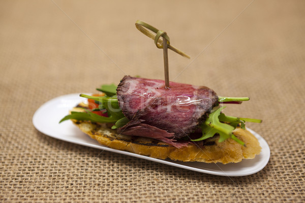 Fresh delicious Spanish tapas with  roast beef  on the textiles background . Great background for re Stock photo © mcherevan