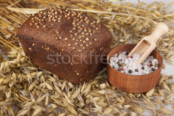Loaf of homemade bread with black mustard seeds on a table with spikelets of rye and salt shaker of  Stock photo © mcherevan