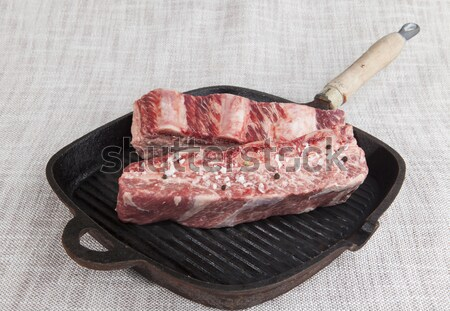 Close-up of two pieces of fresh marbled beef with sea salt and black pepper, knife  on a cast-iron g Stock photo © mcherevan