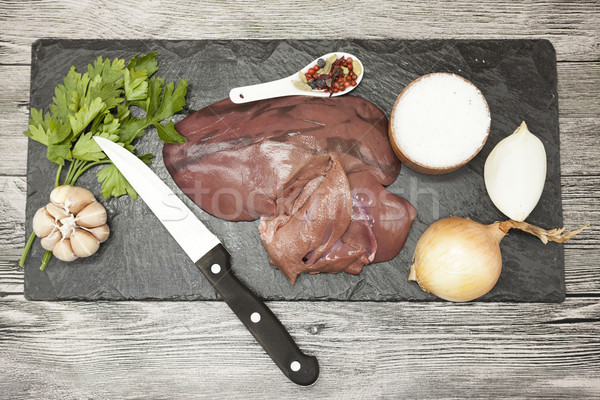 Pieces of fresh raw beef liver, onion, garlic, spices, salt, knife on the stone plate on a white bac Stock photo © mcherevan