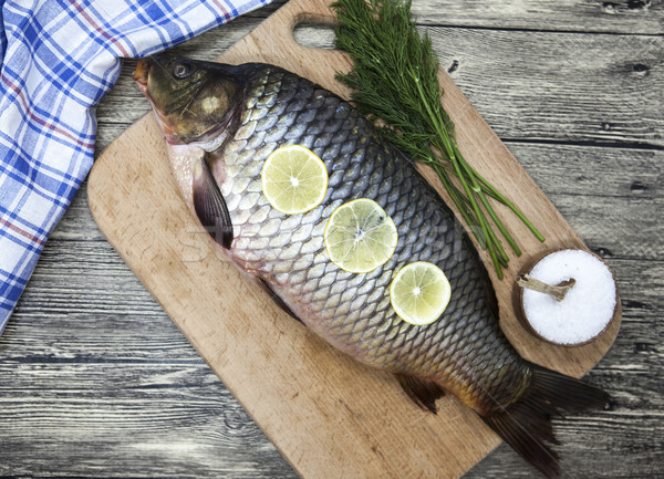 A large fresh carp live fish lying on a with a knife and slices of lemon and with salt dill. Stock photo © mcherevan