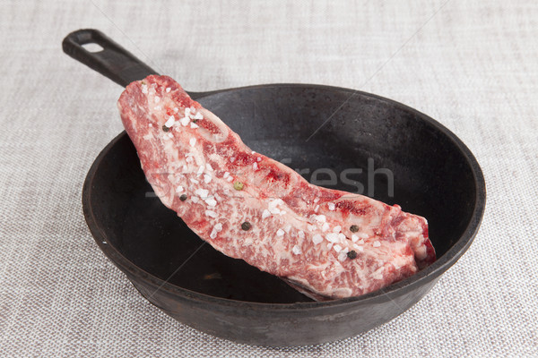Close-up piece of fresh marbled beef with sea salt and black pepper,  on a cast-iron grill pan Stock photo © mcherevan