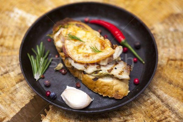Home baked hot sandwich with chicken cheese, onion, chile pepper, garlic  on a cast-iron pan on a wo Stock photo © mcherevan